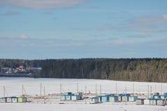 Cabinas de la construcción en la nieve en el campo al lado del bosque y de la carretera construcción de complejos residenciales e imagenes de archivo