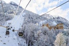 Cabinas de la elevación del sli del cablecarril en el cielo azul y el paisaje hermoso del invierno del fondo nevoso de la montaña Imagen de archivo