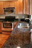 Cabinas de madera de la cocina negras y estufa inoxidable Foto de archivo libre de regalías