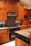 Cabinas de madera de la cocina negras y estufa inoxidable Imagenes de archivo