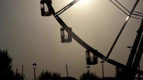 Cabinas de una rueda panorámica en la puesta del sol almacen de metraje de vídeo