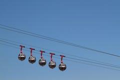 Cabinas del teleférico en los cielos azules Imagen de archivo