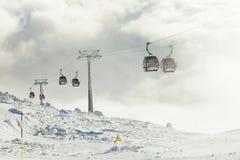 Cabinas del teleférico que entran hacia arriba y hacia abajo en las montañas en un centro turístico de los deportes de invierno Fotos de archivo