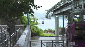 Cabinas del teleférico que mueven encendido la manera de la cuerda para el transporte del pasajero a través del mar en ciudad m almacen de metraje de vídeo