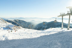 Cabinas del teleférico que van arriba y abajo de alto en las montañas en un centro turístico de los deportes de invierno en un dí Imagenes de archivo