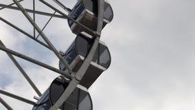 Cabinas Ferris Wheel que gira en un fondo del cielo nublado almacen de metraje de vídeo