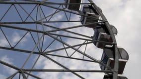 Cabinas Ferris Wheel que gira en un fondo del cielo nublado almacen de video