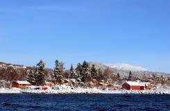 Cabinas nevadas en el fiordo Imagen de archivo libre de regalías