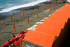 Cabinas y parasoles de playa coloridos por el color coralino del mar fotos de archivo