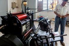 CABINDA/ANGOLA - 8 de junio de 2010 - máquina vieja de la impresión con el operador, en gráficos viejos Fotos de archivo