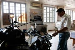 CABINDA/ANGOLA - 8 de junio de 2010 - máquina vieja de la impresión con el operador, en gráficos viejos Foto de archivo libre de regalías
