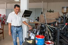 CABINDA/ANGOLA - 8 de junio de 2010 - máquina vieja de la impresión con el operador, en gráficos viejos Imagen de archivo libre de regalías