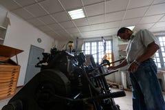 CABINDA/ANGOLA - 8 de junio de 2010 - máquina vieja de la impresión con el operador, en gráficos viejos Fotos de archivo libres de regalías