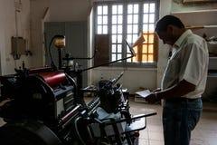 CABINDA/ANGOLA - 8 de junio de 2010 - máquina vieja de la impresión con el operador, en gráficos viejos Imagenes de archivo