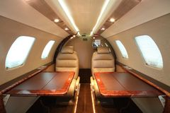 Cabine d'avion à réaction de petite entreprise - élevez, les deux tables Image stock