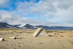 Cabine da madeira lançada à costa na praia em Svalbard com madeira lançada à costa e ossos na praia fotos de stock