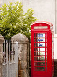 Cabine de téléphone britannique près d'une porte photos stock