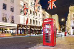 Cabine de téléphone rouge de touristes populaire avec le cric des syndicats de drapeaux dans la nuit l Photos stock