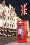 Cabine de téléphone rouge de touristes populaire avec le cric des syndicats de drapeaux dans la nuit l Photo stock