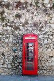 Cabine de téléphone rouge sur le mur en pierre Image libre de droits