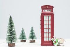 Cabine de téléphone de Toy London, cadeaux et arbres de Noël rouges photo libre de droits