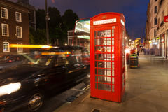 A cabine de telefone vermelha do turista popular na noite ilumina a iluminação dentro foto de stock