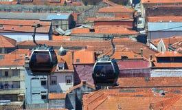 Cabine della cabina di funivia sopra i tetti rossi Immagine Stock Libera da Diritti