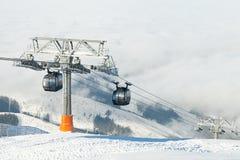 Cabine di funivia che vanno su e giù nelle montagne ad un'area di località di soggiorno degli sport invernali un giorno soleggiat Immagine Stock