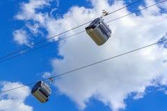 Cabine di una cabina di funivia contro un cielo blu con le nuvole Fotografia Stock