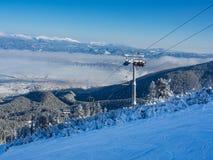 Cabine do teleférico picos em montanha de Bansko, de Bulgária e de neve no fundo Céu azul, 2017 Imagens de Stock
