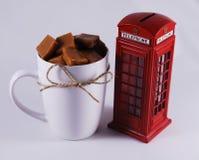 Cabine et tasse de téléphone de l'Angleterre avec le caramel Photo stock