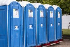 Cabine portatili della toilette del WC della via in un parco Una linea di toilette chimiche per un festival, contro un fondo dell immagine stock libera da diritti
