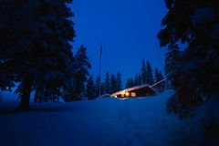 Cabine scandinave de forêt dans la région boisée neigeuse L'hiver en Norvège image stock