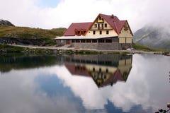 Cabine sur un lac, avec des réflexions dans l'eau. Photo stock
