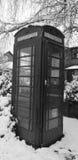 Cabine téléphonique noire et blanche dans la neige photographie stock