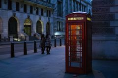 Cabine téléphonique rouge britannique traditionnelle sur la rue de Londres, illuminée de dans le côté la nuit photographie stock libre de droits