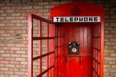 Cabine téléphonique rouge démodée avec la porte ouverte Images libres de droits