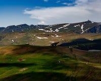 Cabine vermelha aninhada sobre a montanha da com picos nevados na distância fotografia de stock