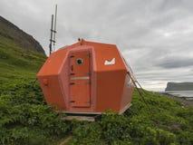 Cabine vermelha do abrigo da emergência em Hornvik que está no prado da grama da costa de mar com vista em penhascos do hornbjarg imagem de stock
