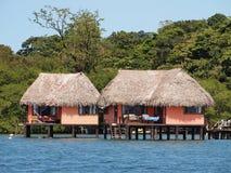 Cabines avec le toit couvert de chaume au-dessus de l'eau Photo libre de droits