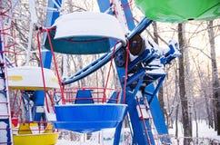 Cabines colorées de roue de ferris sous la neige fermée Images stock