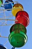 Cabines coloridas da roda de ferris contra o céu azul Imagem de Stock