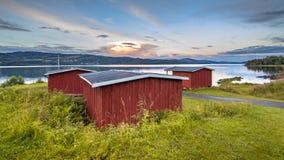 Cabines de madeira vermelhas na margem do lago em Noruega fotos de stock
