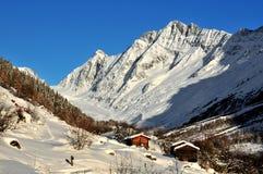 Cabines e montanhas de registro na neve Fotos de Stock Royalty Free