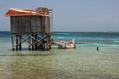 Cabines op stelten op het kleine eiland van Tabak Caye, Belize Stock Afbeelding