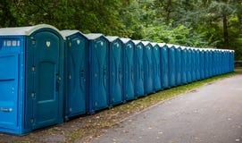 Cabines portatives de carte de travail en parc Une ligne des toilettes chimiques pour un festival, contre une forêt images stock