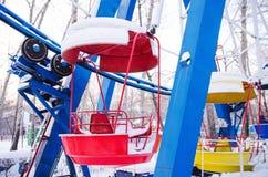 Cabines rouges et jaunes de roue de ferris sous la neige, hors du gea Photos libres de droits
