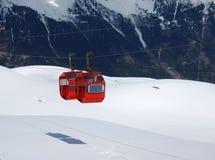 Cabines vermelhas do cabo aéreo de encontro à montanha Imagens de Stock Royalty Free