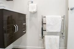 Cabinet at basin and white towel on metal rails for taking a bath. In bathroom Royalty Free Stock Photo