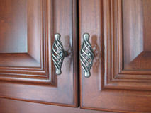 Cabinet Hardware. Cherry Cabinets with Scrolled Hardware Stock Photos